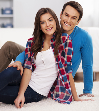 Young couple enjoying carpet in their home.